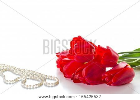Bouquet of red roses and a pearl necklace on a white background.