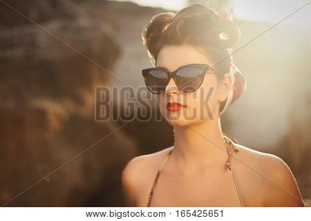 Beautiful woman on the beach with red sensual lips. Pretty girl spending vacation on the sea.