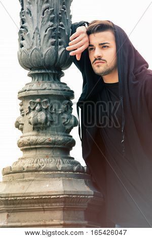Mysterious and handsome young man with hoody against a lamppost.