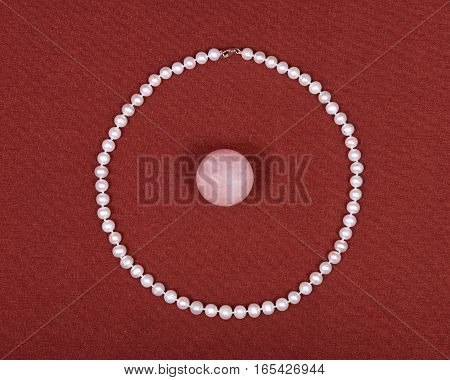 Freshwater pearl necklace and pink rose quartz ball on red fabric background