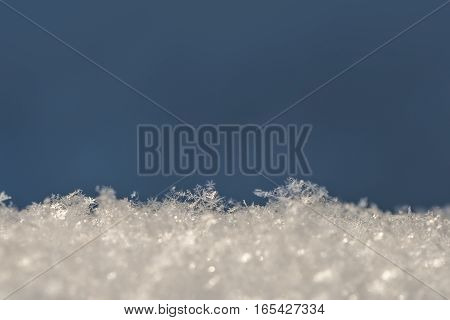 background with snow crystals on blue at winter