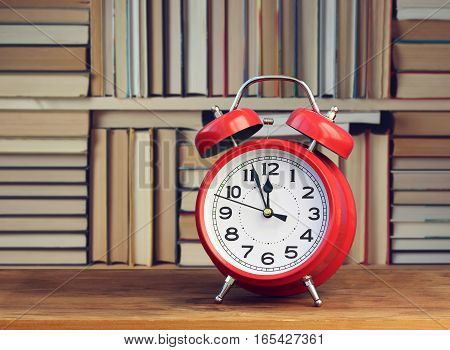 Red retro alarm clock at twelve o'clock on the background of the bookcase. Library.