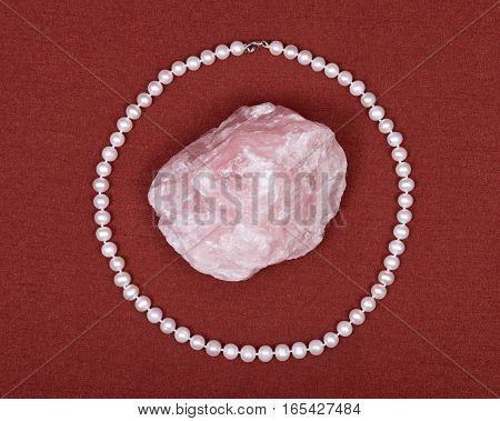Freshwater white pearl necklace and pink rose quartz gemstone on red fabric background