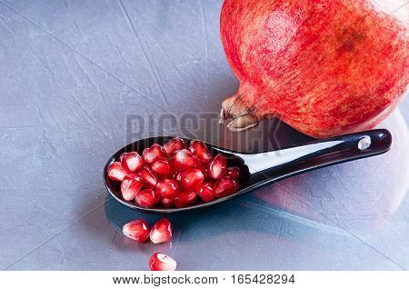 a pomegranate seeds in a ceramic spoon and a sprig of rosemary on a dark surface