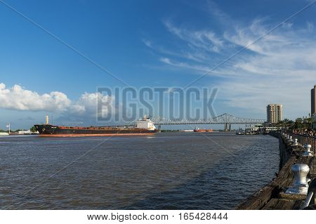 New Orleans Louisiana USA - June 17 2014: View of the Mississippi River in the New Orleans riverfront with cargo ships navigating in the river.