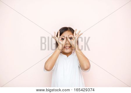 Asian Tanned Skin Girl Child Portrait Over Pink Wall Background Shows Hands As Eyeglass Wow Concept.