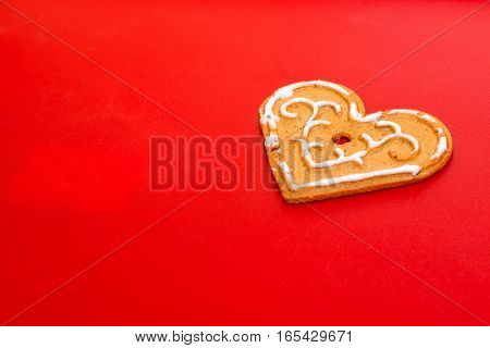 Cookies in shape of heart for Valentine's Day on on background of red matte plastic. Festive treat for celebrating lovers. Holiday gingerbread with icing on polymer texture