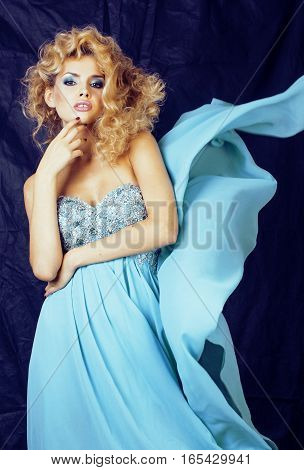 young pretty blond woman in blue luxury dress, studio blue background