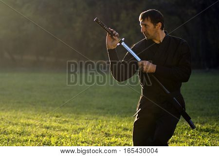 Ninja in black kimono with sword is outdoors in the park.