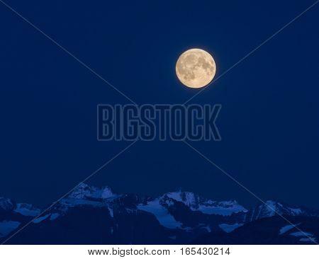 A full moon shines bright white over the blue shrouded Kenai Mountains.