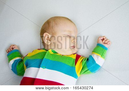 small baby in striped suit lying on a light blanket