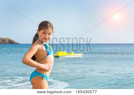 Cute happy girl child in blue swimsuit relaxing and bathed on shores of Cretan sea. Sunny sandy Livadi beach in sea Bay of resort village Bali Rethymno Crete Greece