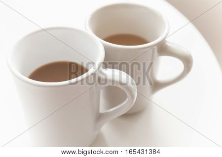 Two Mugs Full Of Coffee With Milk