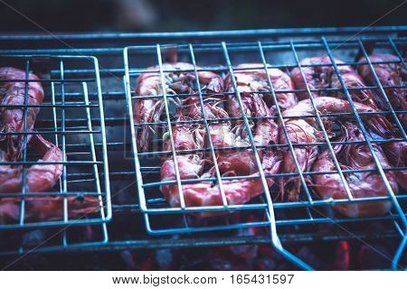 Delicious barbecue prawns cooking on grill with hot red charcoal