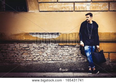 Handsome young man on the street leaning against the wall. A beautiful model with a black bag is waiting leaning against an ancient wall of an old building.
