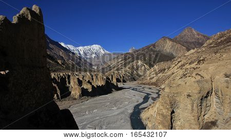 Marsyangdi river and limestone cliffs. Snow capped Tilicho Peak. Scenery in Manang Annapurna Conservation Area.