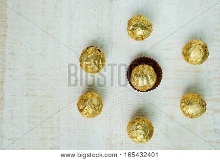 Chocolate ball wrapped in foil Chocolates arranged in a circular shape chocolate background
