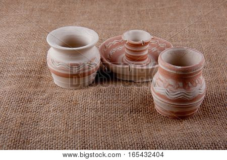 Pottery. Two jugs and candlestick with patterns made of clay on sackcloth background