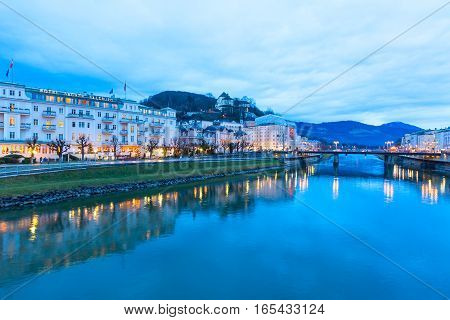 Salzburg, Austria - December 25, 20016: Evening twilight view of historic city of Salzburg with illuminated houses across Salzach river in Austria