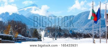 Bansko ski resort panorama with cable car ski lift cabin, bulgarian flag and snow mountains