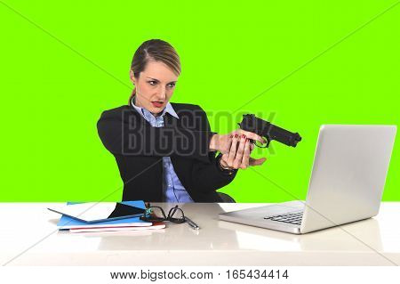 young attractive businesswoman pointing gun to computer laptop sitting at office desk desperate and stressed having problems with work project and technology isolated green chroma key