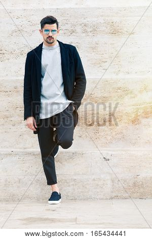 Handsome man with sunglasses and fashionable clothes leaning against a marble wall white