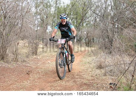 Middle Aged Man Enjoying Outdoors Ride At Mountain Bike Race