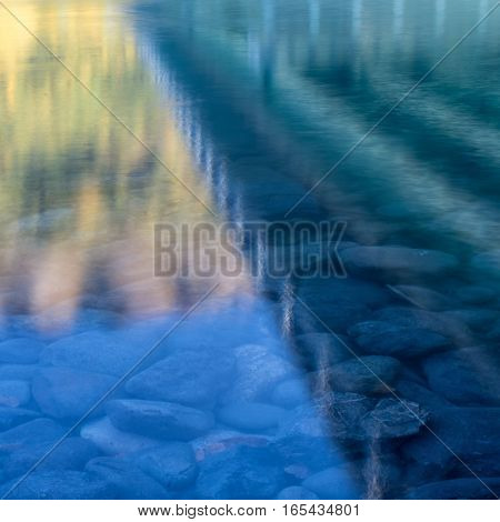 Slight ripples betray the flowing water reflecting the image of a bridge.
