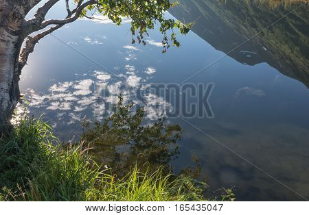 A still pond acts like a mirror and reflects a crystal clear view of an Alaskan hillside.