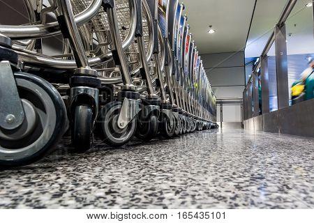 Floor view of airport trolleys. Travelers passing by.