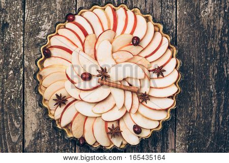Apple pie tart on the rustic wooden background. Ingredients - apples and cinnamon .Top view.