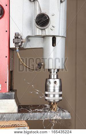 Drilling hole in metal metalworking industry drilling a hole on modern metal working machining center metal hole saw bit.