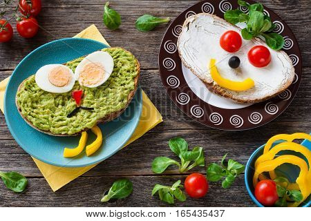 Funny colorful creative meal idea for kids: avocado sandwich with hard boiled egg, pepper nose and black olive mustage; cream cheese sandwich with vegetable face and corn salad
