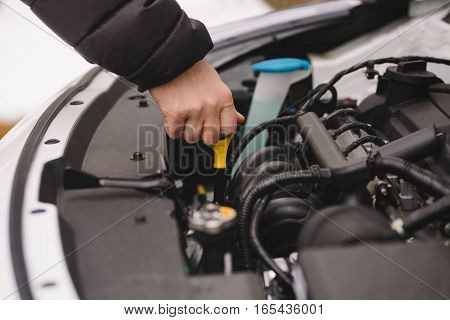 Car maintenance before winter. Man checking oil level in his car using dipstick. Outdoor closeup photograph