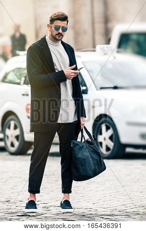 Handsome man model with sunglasses and cell phone standing outdoors with urban traffic behind. The boy dresses fashionable, wearing sunglasses, trousers with a flap, a black bag in his hand.