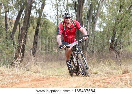 Smiling Middle Aged Man Enjoying Outdoors Ride At Mountain Bike Race