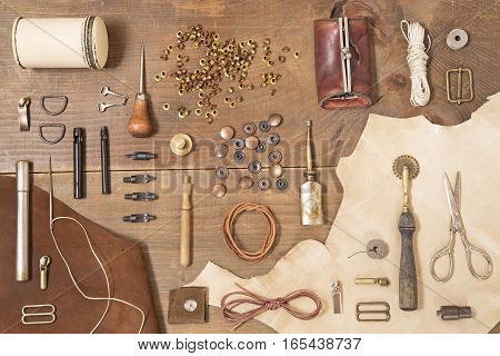Leather craft tools on brown wooden background