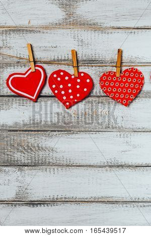 handmade toy hearts hanging from a rope on a white wooden background. Valentine day background. Vertical image.