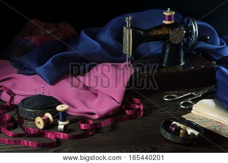 Old sewing machine, fabrics, scissors and other accessories on a dark wooden table