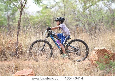 Young Inian Boy Riding Through Bush At Mathaithai Mountain Bike Race