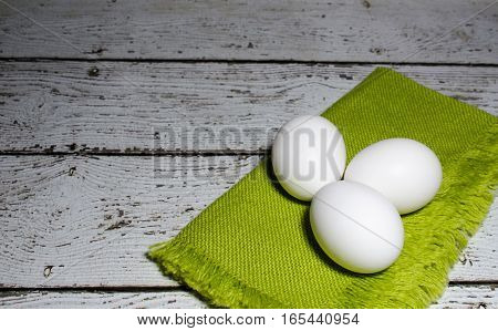 Three raw chicken eggs ready to color for Easter or use for baking.  Space for text.