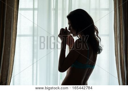 Woman drinking from a cup. Lady near window. Sip of warm coffee.