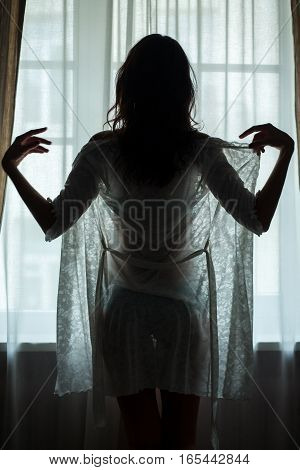 Female standing near window. Back view of young woman. Beauty will save the world.