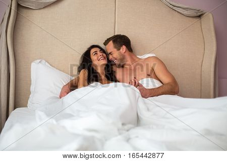 Couple laughing in bed. Happy man and woman. Good morning, my love.