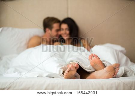 Couple's feet under blanket. Caucasian woman and man indoor. Home comfort and romance.