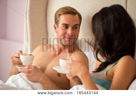 Couple with cups in bed. Young man looking at woman. Our morning starts from coffee.