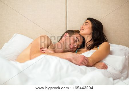 Lady with man in bed. Smiling people with closed eyes. Days spent together are priceless.