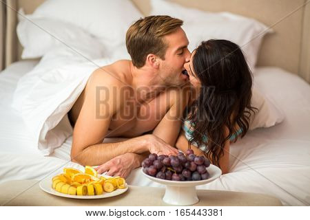 Couple eats grapes in bed. White plates with fruits. Sweetness of love.