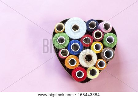 Colorful threads in heart shape on pink background