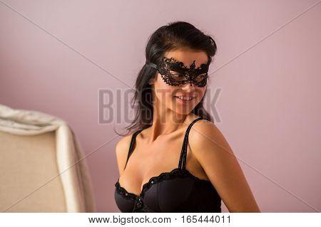 Woman wearing black lace mask. Lady in bra. Enchantress of passion.
